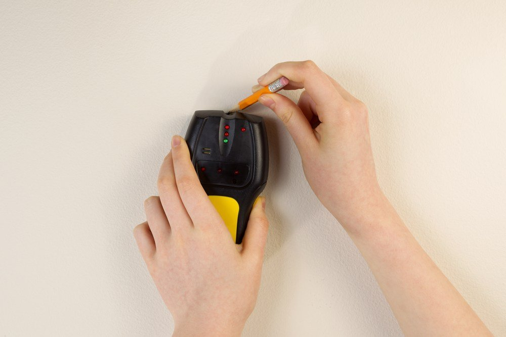female hands demonstrating how stud finder works to locate studs behind sheetrock