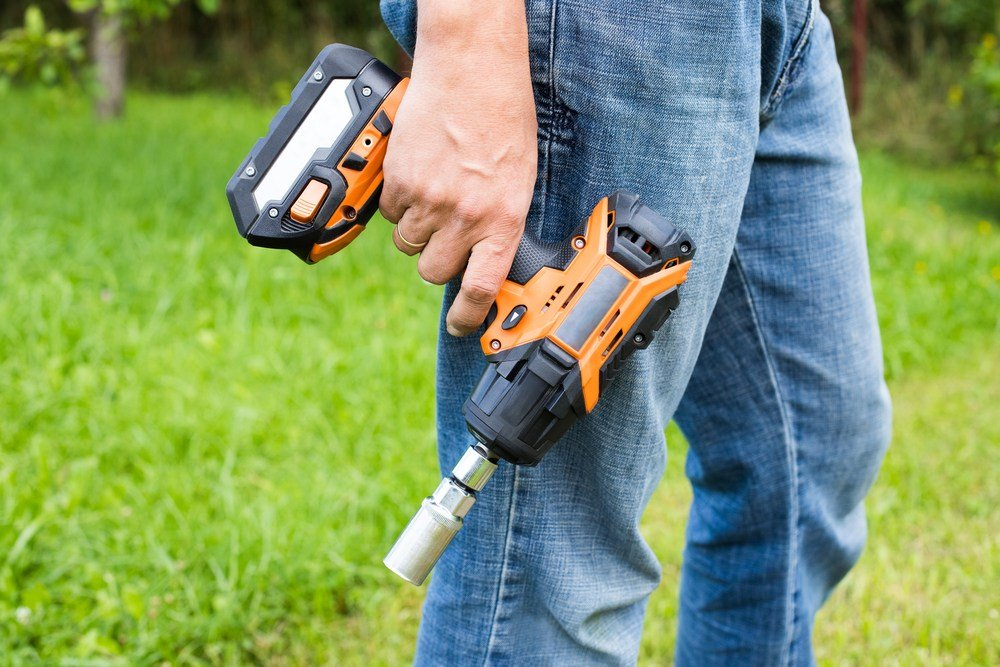 Image of Mechanic carrying the best cordless impact wrench with a socket attached