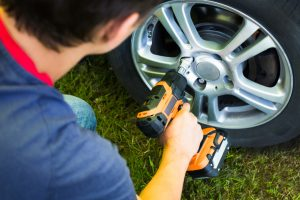Close Up Of Young Mechanic Changing Wheel On Car With Accumulator Impact Wrench Outdoor Top View.
