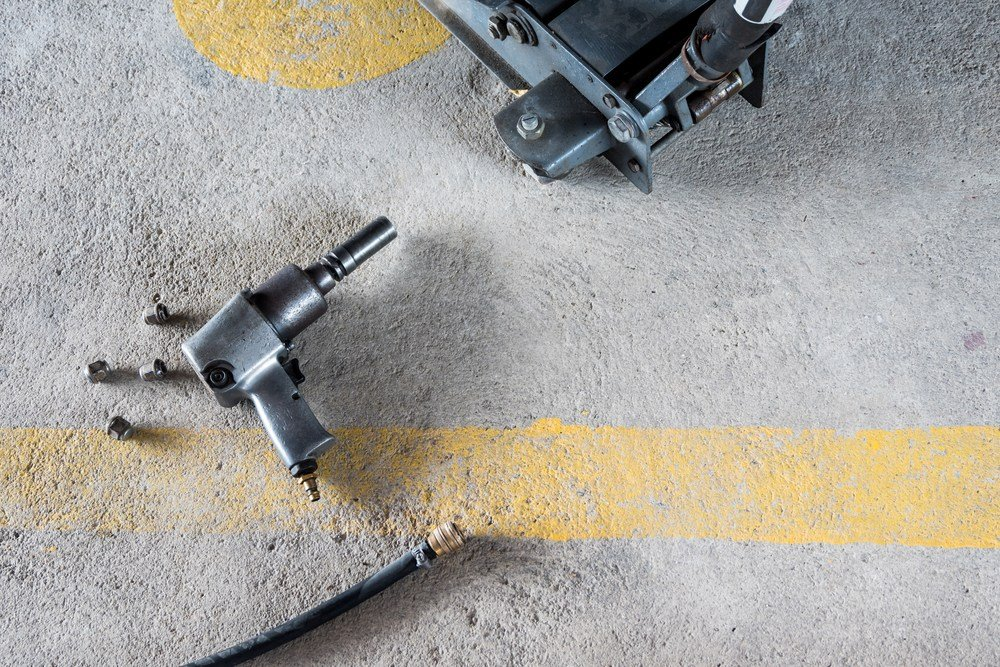 Air impact wrench lying on the floor with air hose nearby