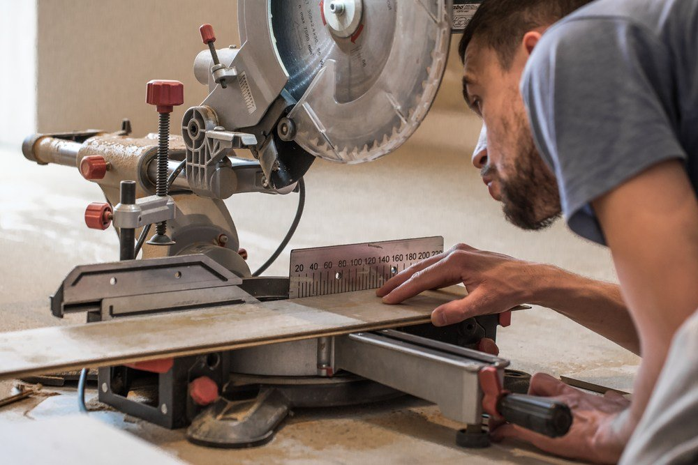 man aligning his miter saw for a cut