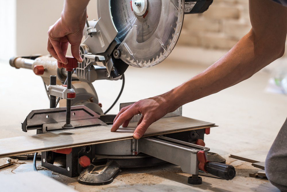 closeup of a man lining up a compound sliding miter saw for a cut