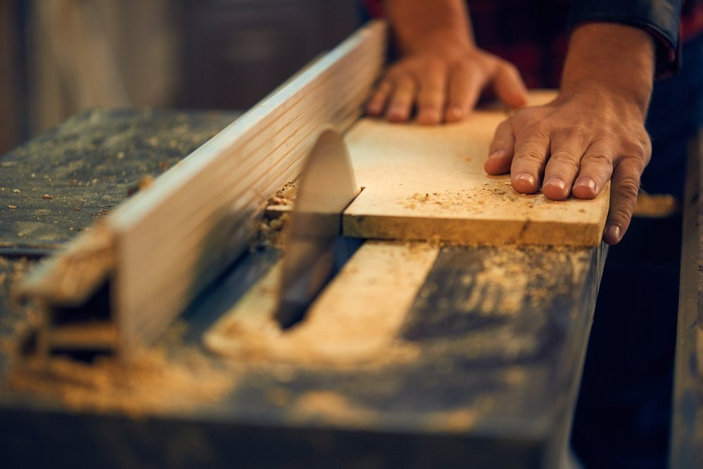 image of hands feeding wood into table saw