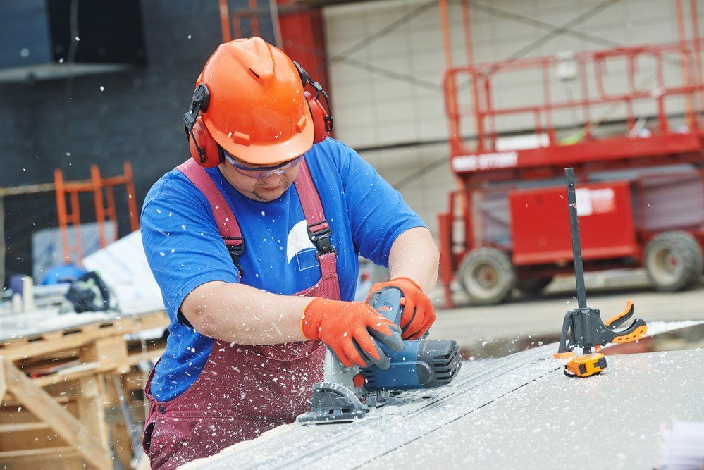 image of construction worker in organge hard hat using a track saw