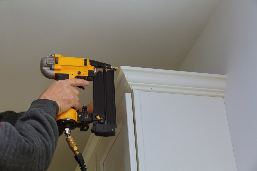 carpenter using yellow brad nailer on white crown molding