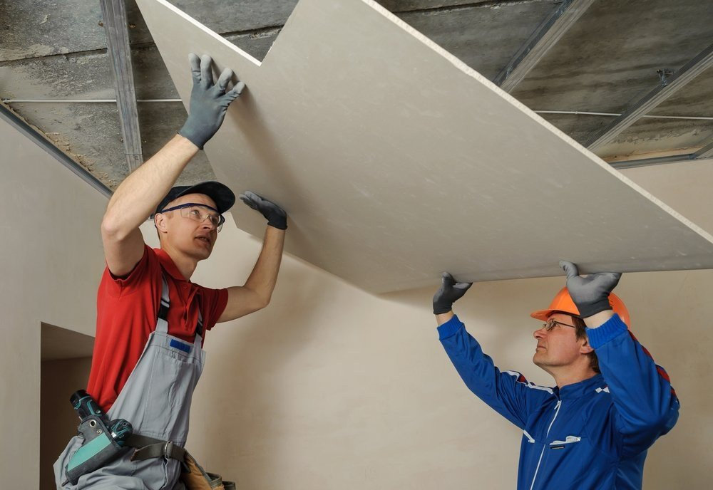 image of two drywall installers lifting a custom cut gypsum panel over their head