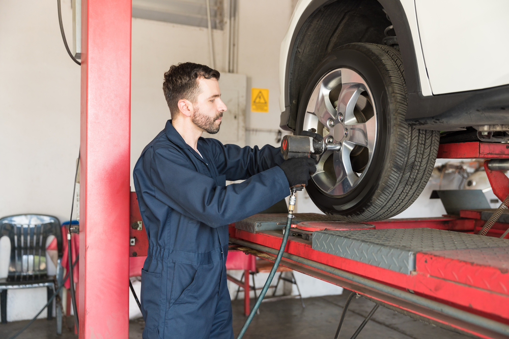 Mechanic Tightening Nuts On Tire With Impact Wrench