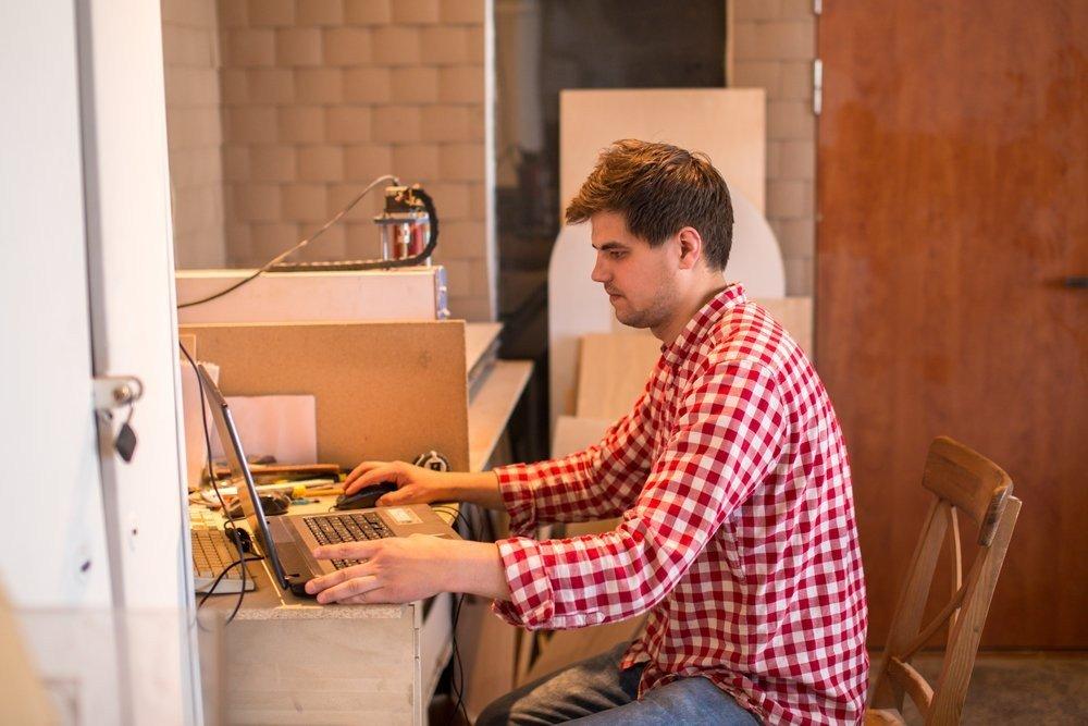 Carpenter worker prepares a computer program software for CNC machine,