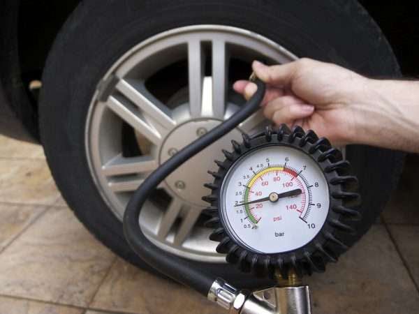 image of manometer and hand checking tire