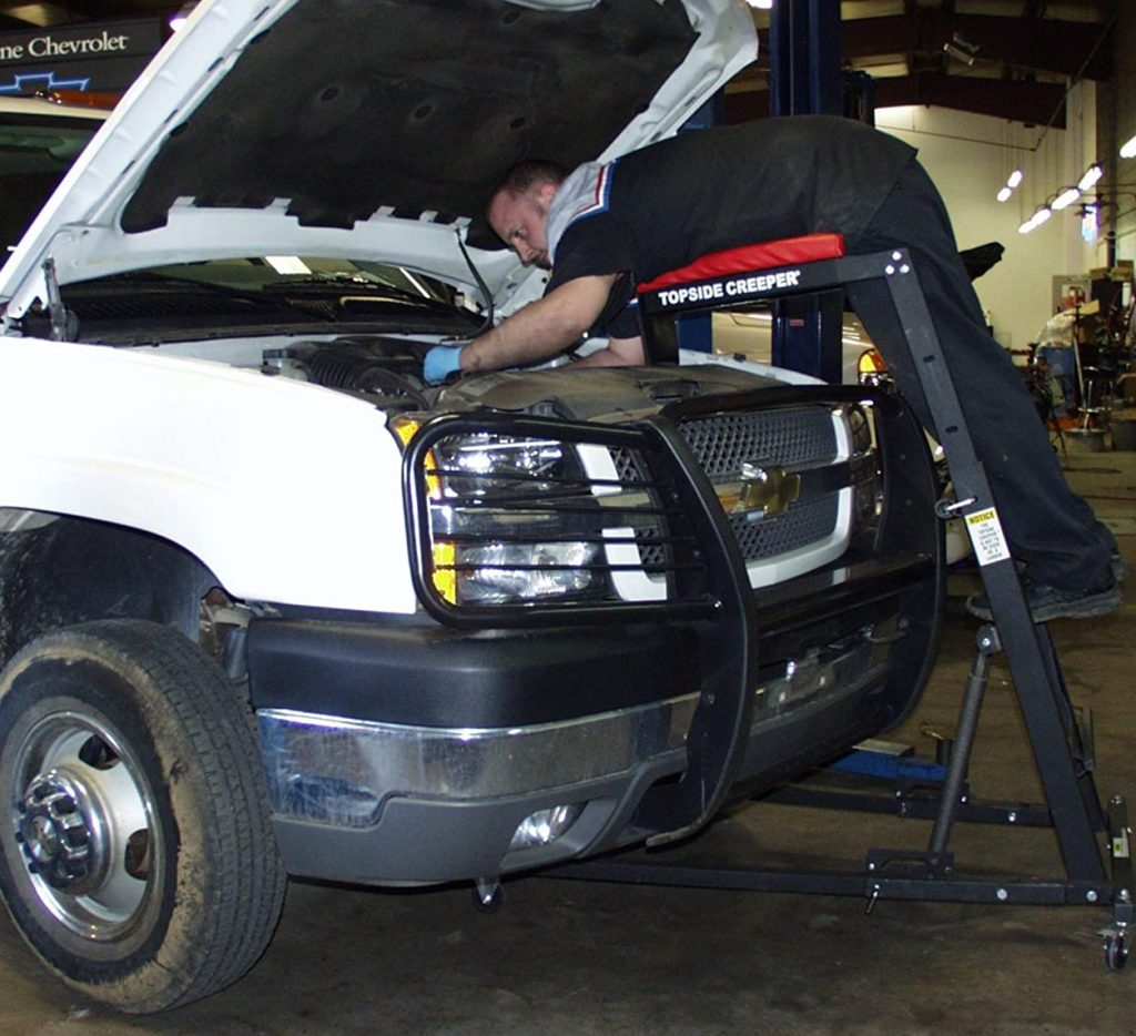 image of mechanic using topside creeper to work on GMC truck
