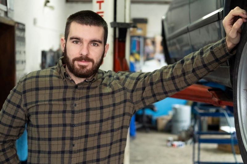 Zachary Drumm Leaning on Car in Auto Shop