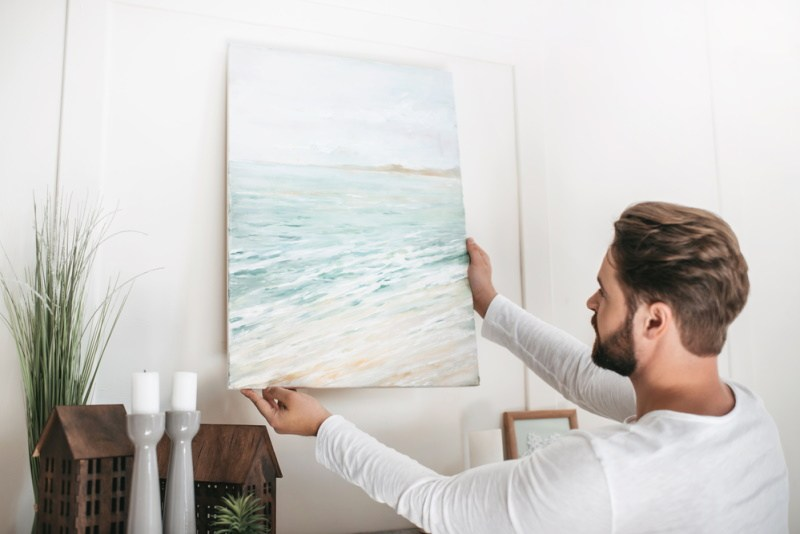 young bearded man hanging a photo