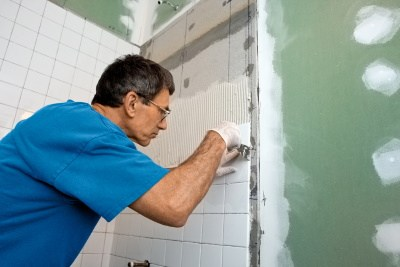 image of man applying tile to hardieboard in a bathroom. Greenboard is present as the mold-resistant drywall.