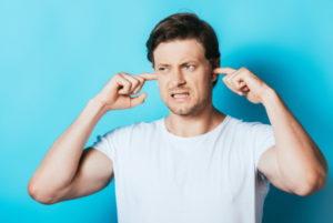 man holding fingers in ears